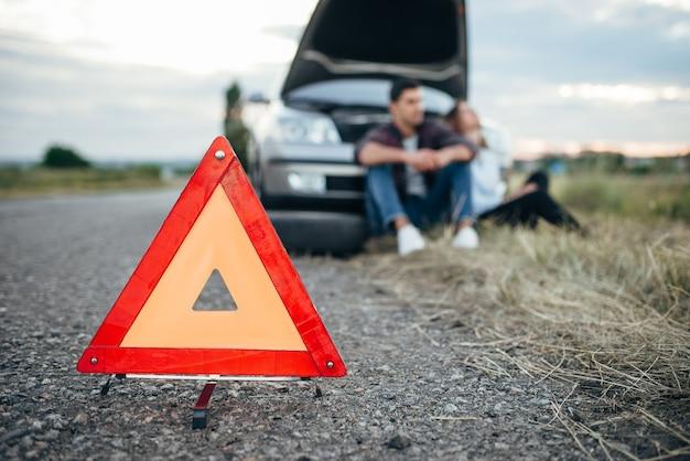 Koncepcja złamanego samochodu, mężczyzna siedzi na oponie