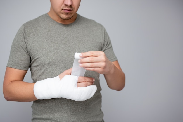 Koncepcja złamania i pierwszej pomocy - zbliżenie młodego mężczyzny bandażującego rękę po wypadku i miejsca kopiowania na szarym tle ściany