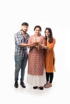 Koncepcja złotej pożyczki lub kredytu hipotecznego - hinduska matka z synem i córką trzymającą złotą biżuterię