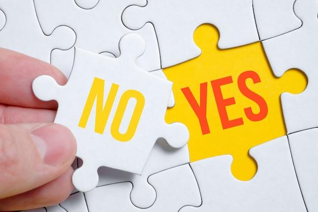"""Koncepcja zmiany pozycji z """"nie"""" na """"tak"""". kawałek układanki trzyma mężczyzna palcami"""
