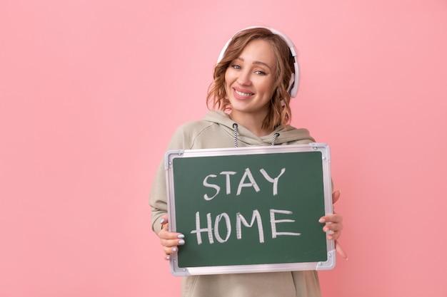 """Koncepcja """"zostań w domu"""" pozytywna wiadomość kobieta ze słuchawkami ubrana w obszerną bluzę z kapturem trzyma tablicę z napisem """"zostań w domu""""."""
