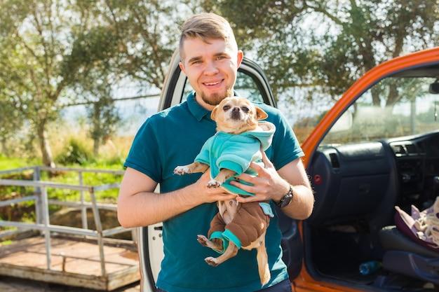 Koncepcja zwierząt domowych, zwierząt domowych, pory roku i ludzi - portret szczęśliwego mężczyzny z psem chihuahua spacerującym na zewnątrz