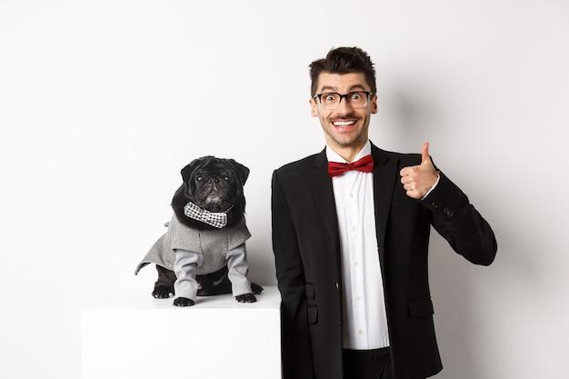 Koncepcja zwierząt, imprez i uroczystości. przystojny młody mężczyzna w garniturze i ładny czarny mops w stroju, patrząc na kamerę, właściciel pokazuje kciuk w aprobacie i pochwałach, białe tło