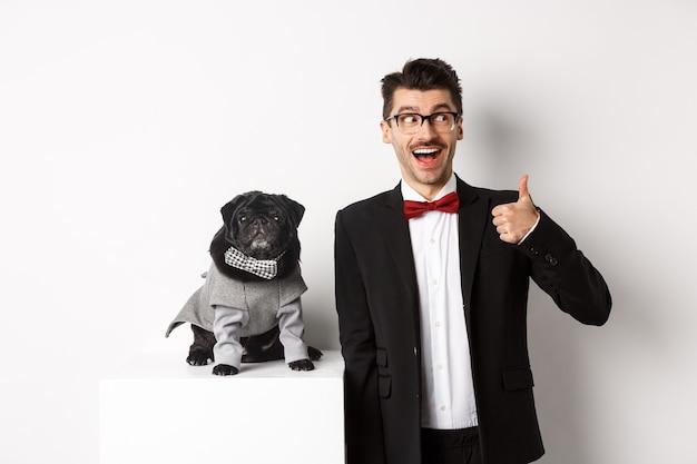 Koncepcja zwierząt, strony i uroczystości. przystojny młody mężczyzna w garniturze i ładny czarny mops w kostiumie wpatrując się w kamerę, właściciel pokazując kciuk do góry z aprobatą i pochwałą, biały.