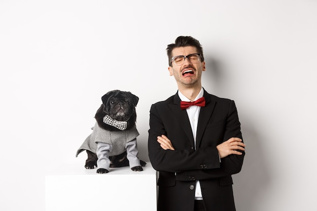 Koncepcja zwierząt, strony i uroczystości. smutny właściciel psa płacze, ubrany w garnitur, stojący w pobliżu ślicznego czarnego mopsa w kostiumie, stojący nad białym.