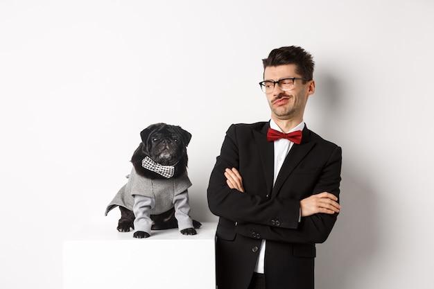 Koncepcja zwierząt, strony i uroczystości. wizerunek zabawny młody człowiek w garniturze i okularach, patrząc sceptycznie na ładny mops w kostiumie, stojąc na białym.