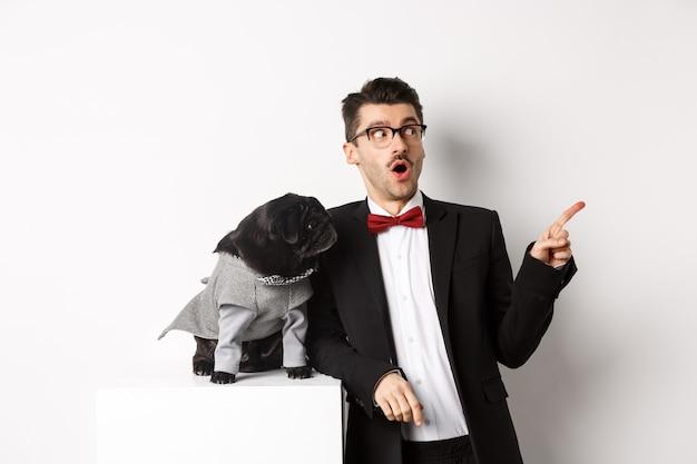 Koncepcja zwierząt, strony i uroczystości. zdziwiony młody człowiek i czarny pies w kostiumach wpatrując się w przestrzeń kopii, stojąc na tle bieli