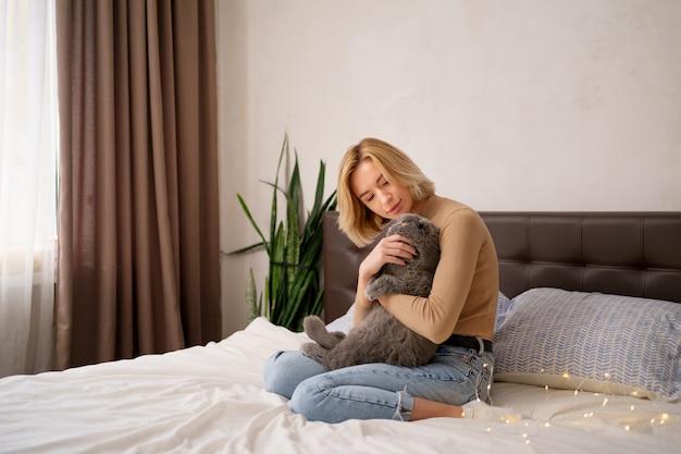 Koncepcja zwierzęta, poranek, komfort, odpoczynek i ludzie - szczęśliwa młoda kobieta z kotem w łóżku w domu