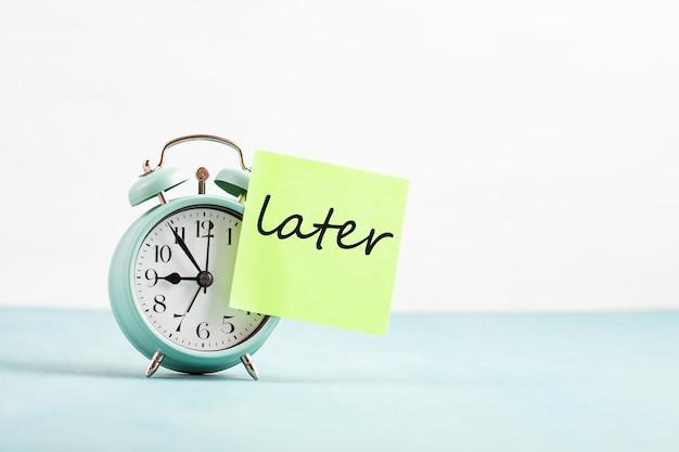 Koncepcja zwlekania, opóźnienia i pilności. złe zarządzanie czasem. słowo później przykleiło się do budzika