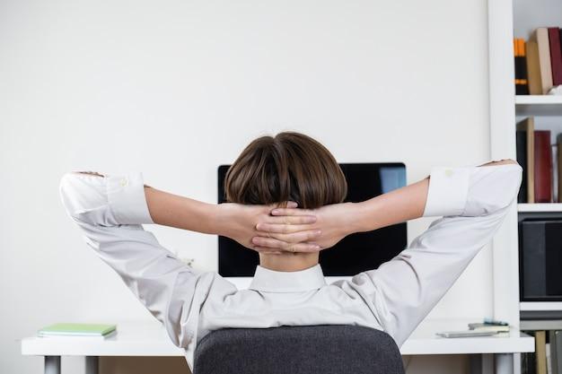 Koncepcja zwlekania: pracownik biurowy rozciągający się przed czarnym ekranem komputera. żeńskiego pracownika obsiadanie przy biurkiem i mieć odpoczynek przy miejscem pracy