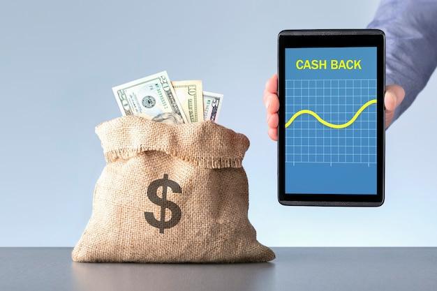 Koncepcja zwrotu gotówki. człowiek posiadający cyfrowy tablet z wykresem wzrostu w pobliżu torby z dolarami.