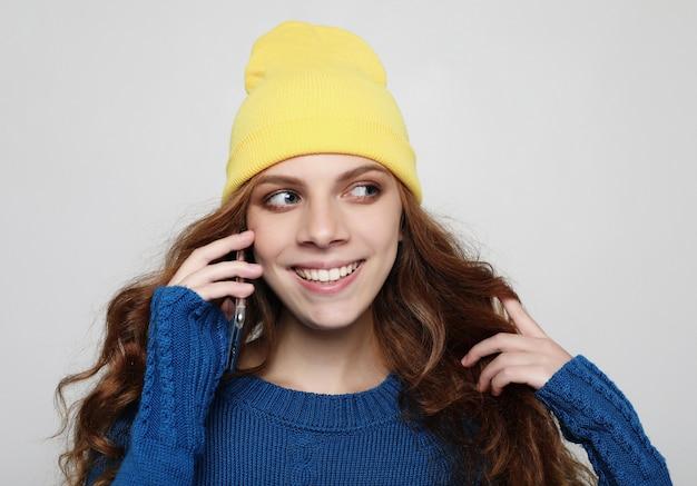 Koncepcja życia, emocji i ludzi. młoda kędzierzawa kobieta z mądrze telefonem