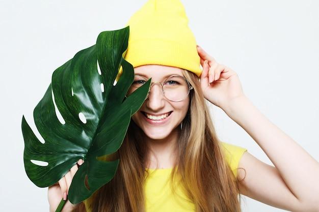 Koncepcja życia, emocji i ludzi: uśmiechnięta kobieta za duży liść