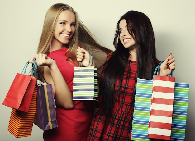 Koncepcja życia i ludzi: dwie młode kobiety na sobie czerwoną sukienkę z torbami na zakupy. wielka wyprzedaż.