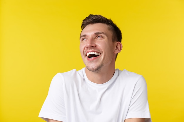 Koncepcja życia, lato i ludzie emocje. szczegół portret beztroskiego szczęśliwego przystojnego mężczyzny, patrząc w lewym górnym rogu baner i śmiejąc się, stojąc w podstawowym białym t-shrit na żółtym tle.