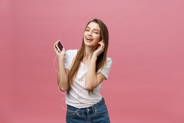 Koncepcja życia. młoda kobieta używa telefon dla słuchać muzyka na różowym tle
