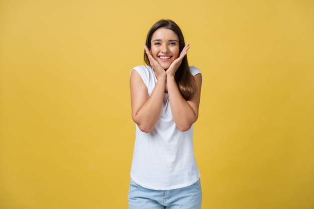 Koncepcja życia - portret młodej dziewczyny stylowe śmiejąc się z ręką na brodzie patrząc na kamery. żółte złoto tło. skopiuj miejsce.