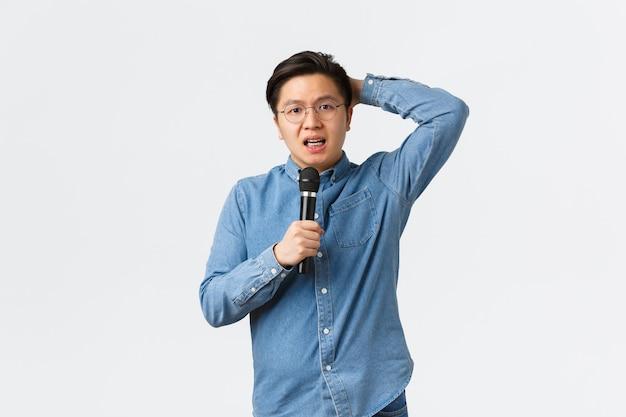 Koncepcja życia, wypoczynku i ludzi. nieśmiały i niepewny azjatycki facet stojący niezdecydowany na białym tle z mikrofonem, boi się przemawiać publicznie, stojąc zaniepokojony białym tłem.