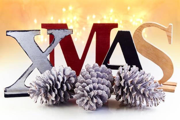 Koncepcja życzenia świąteczne. drewniane litery xmas i oszronione szyszki na tle świecącej girlandy.