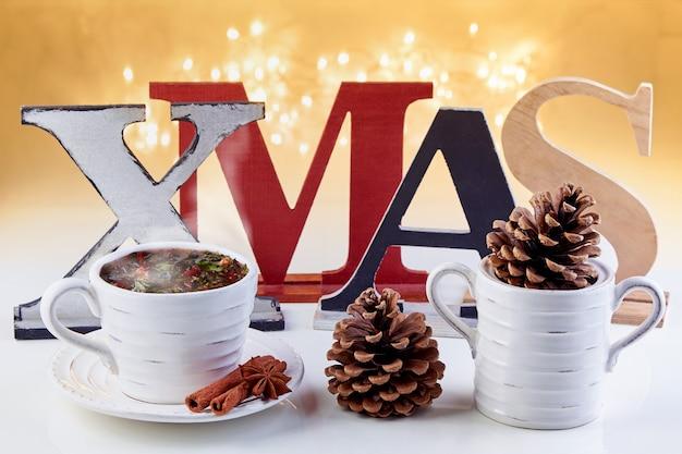 Koncepcja życzenia świąteczne. gorący napój świąteczny i napisy xmas na tle świecącej girlandy