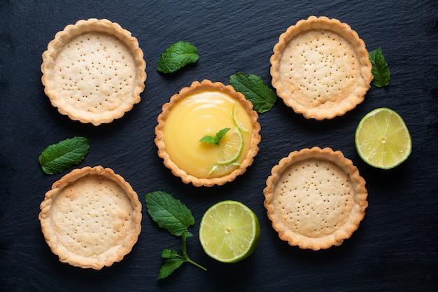 Koncepcja żywności domowa ekologiczna cytryna, limonki lub mini ciasto na czarnej płycie z łupków