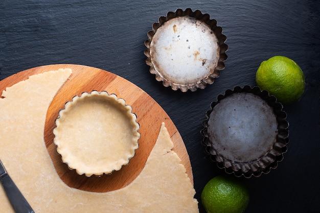 Koncepcja żywności domowa pusta skorupa do ekologicznej cytryny, tarty z limonki lub mini ciasto na czarnej łupkowej kamiennej płycie