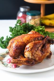 Koncepcja żywności domowej roboty pieczony, z grilla cały organiczny kurczak na białym talerzu ceramicznym