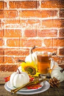 Koncepcja żywności dziękczynienia. jesienny stół z talerzem, filiżanką herbaty, dyniami, słonecznikiem i ciepłą kratą