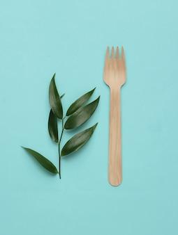 Koncepcja żywności ekologicznej drewniane widelce zielone liście na niebieskim tle pastelowych