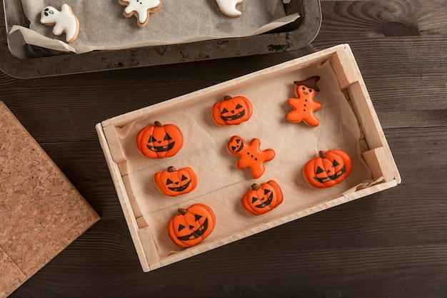 Koncepcja żywności halloween. śmieszne pomarańczowe ciasteczka w kształcie dyni i mężczyzn leżą w formie na stole. halloweenowa uczta