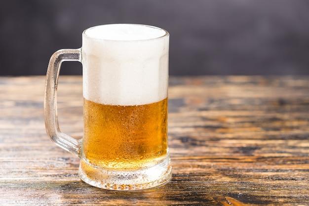 Koncepcja żywności i napojów - piwo szklane na ścianie z drewna z miejsca na kopię.