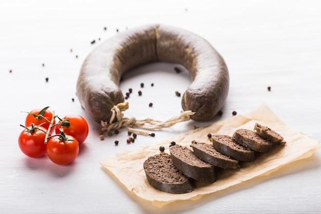 Koncepcja żywności, kuchni i koniny - zamknij się kiełbasa mięsna z pomidorami i pieprzem na kraft