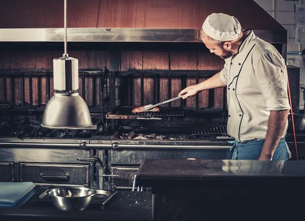 Koncepcja żywności. młody kucharz w białym mundurze monitoruje stopień wypieczenia i obraca mięso kleszczami we wnętrzu nowoczesnej kuchni restauracyjnej. przygotowanie tradycyjnego steku wołowego na piecu grillowym