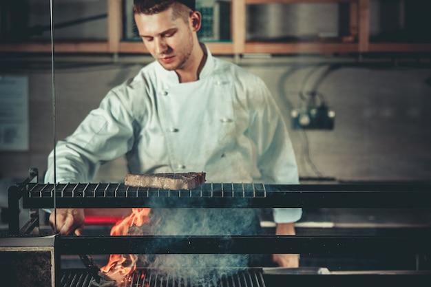 Koncepcja żywności młody przystojny szef kuchni w białym mundurze monitoruje stopień pieczenia i obraca mięso
