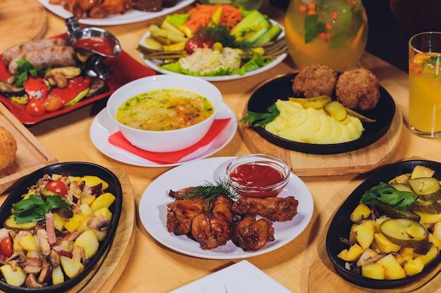 Koncepcja żywności obiadowej. stół obiadowy z grillowaną kiełbasą, opakowaniami tortilli, napojem piwnym i różnymi potrawami na drewnianym stole w stylu rustykalnym.