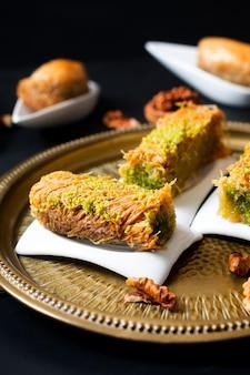 Koncepcja żywności orientalne arabskie deserowe baklava orzechy włoskie i walcowane kanafeh na czarnej płycie łupkowej