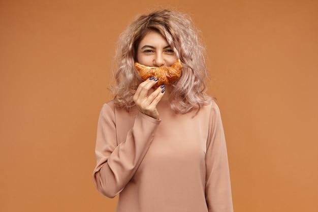 Koncepcja żywności, piekarni i pasty. zdjęcie uroczej uroczej młodej kobiety rasy kaukaskiej z niechlujnymi różowawymi włosami o wesołym wyrazie twarzy