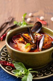 Koncepcja żywności tajskie kwaśne czerwone curry małże ananas kang kua hoi w zielonej misce ceramicznej na niebieskim tle serwetki z drewna z miejscem na kopię