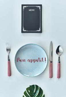 Koncepcja żywności. ujęcie pod wysokim kątem pustego talerza, widelca, łyżki, noża zamkniętego menu leżącego naprzeciw