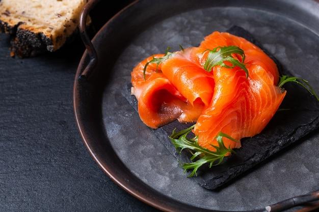 Koncepcja żywności wędzony pstrąg lub łosoś ryby plastry na czarnej płycie łupkowej kamiennej z miejsca na kopię