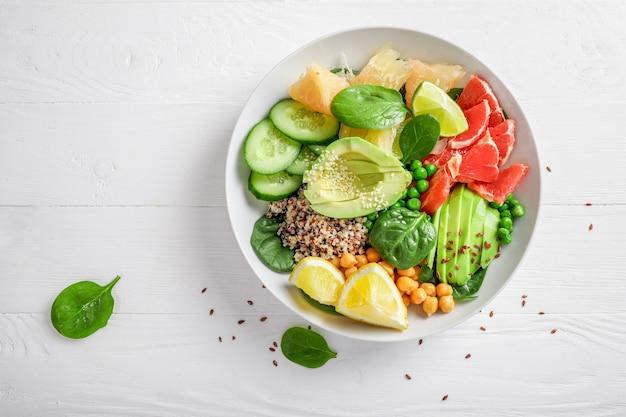 Koncepcja żywności wegańskiej: quinoa z awokado, ogórkami, zielonym groszkiem, ciecierzycą, szpinakiem i owocami cytrusowymi na białym tle. widok z góry.