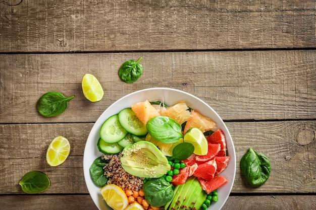 Koncepcja żywności wegańskiej: quinoa z awokado, ogórkami, zielonym groszkiem, ciecierzycą, szpinakiem i owocami cytrusowymi na drewniane tła.