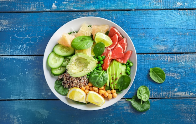 Koncepcja żywności wegańskiej: quinoa z awokado, ogórkami, zielonym groszkiem, ciecierzycą, szpinakiem i owocami cytrusowymi na niebieskim drewnianym backround. widok z góry.