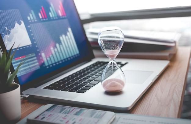 Koncepcje biznesowe z biznesmenem trzymając klepsydrę z wykresu
