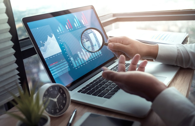 Koncepcje biznesowe z biznesmenem trzymając szkło powiększające z wykresu