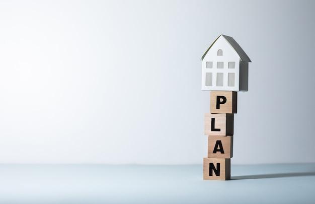 Koncepcje nieruchomości lub nieruchomości z tekstem planu i modelem domu. inwestycje biznesowe i finansowe.