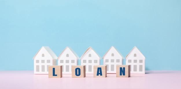 Koncepcje nieruchomości z tekstem pożyczki i modelem domu. inwestycje biznesowe i finansowe.