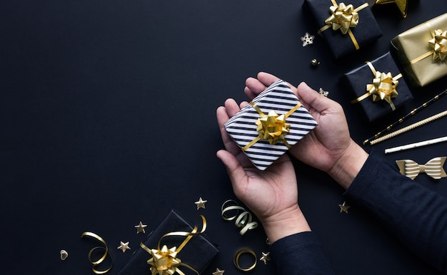 Koncepcje obchodów wesołych świąt i nowego roku z ręką osoby trzymającej pudełko i ornament w złotym kolorze na ciemnym tle. sezon zimowy i dzień rocznicy