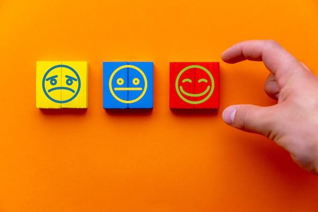 Koncepcje oceny obsługi klienta i badania satysfakcji. ręka klienta wybrała ikonę uśmiechniętej buźki na drewnianej kostce na pomarańczowym tle. skopiuj miejsce
