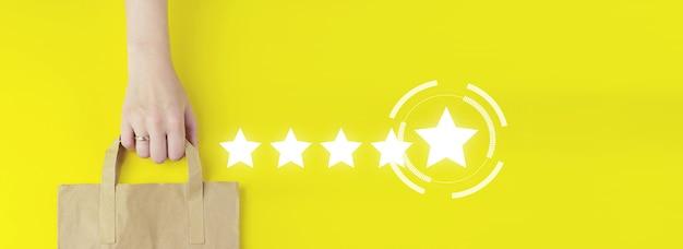 Koncepcje oceny obsługi klienta i badania satysfakcji. torba na zakupy z recyklingu brązowego papieru w ręku z hologramem pięć gwiazdek 5 ocena ikona na żółtym tle, płaskie świeckich. koncepcja sprzedaży letniej.